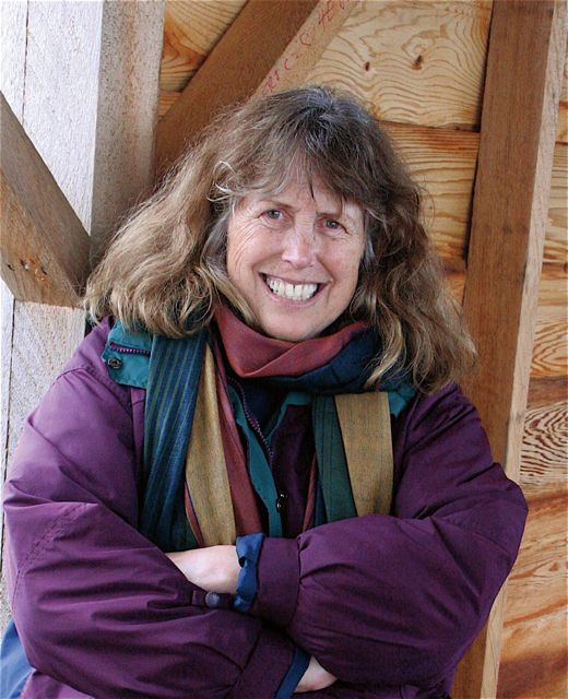 Cheryl Samuel stands smiling in a wooden building.