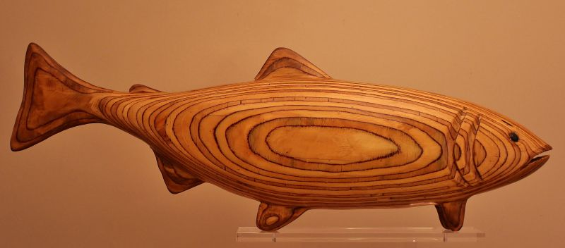 A large wooden salmon carving showing flowing wood grain.