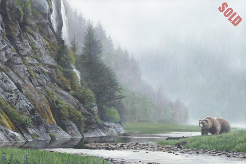 A grizzly stands beside a river beneath a rock cliff in a misty valley.