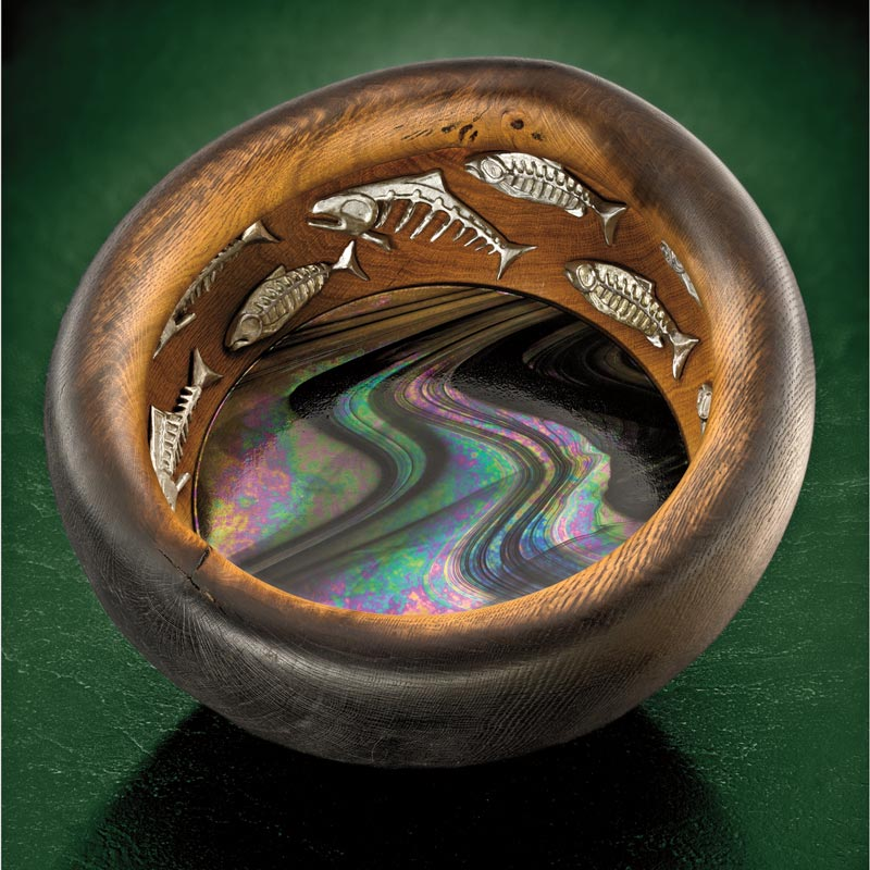 A large bowl made of Garry oak, inlaid with pewter salmon and with a rich shimmering glass bottom.