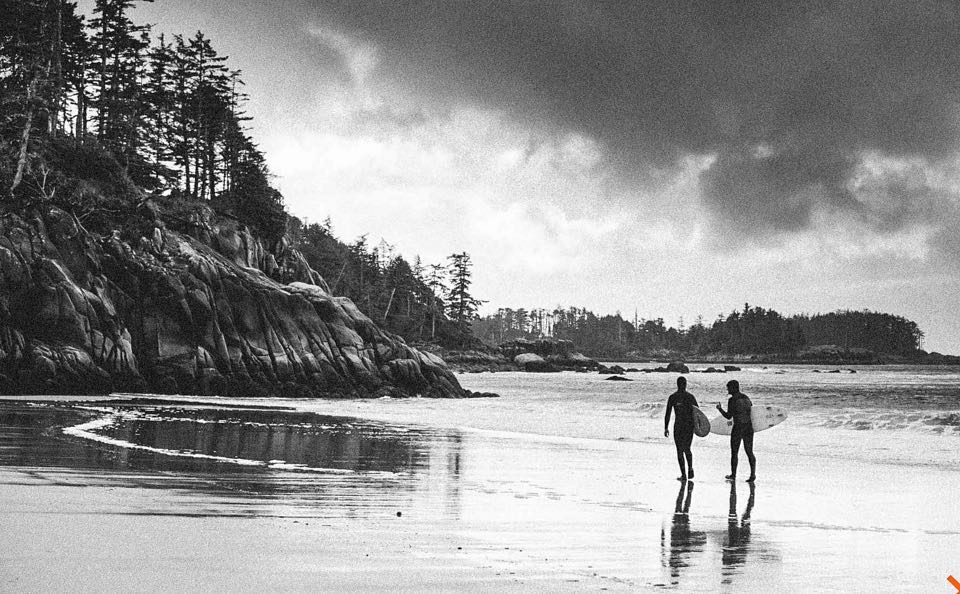 Surfers in Tofino walking out on the beach with their sticks.