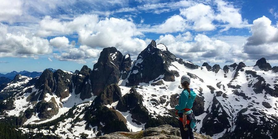 This is a photo of a person in a blue jacket on top of a mountain with dark, snow covered mountains infront of her on a clear sunny day.