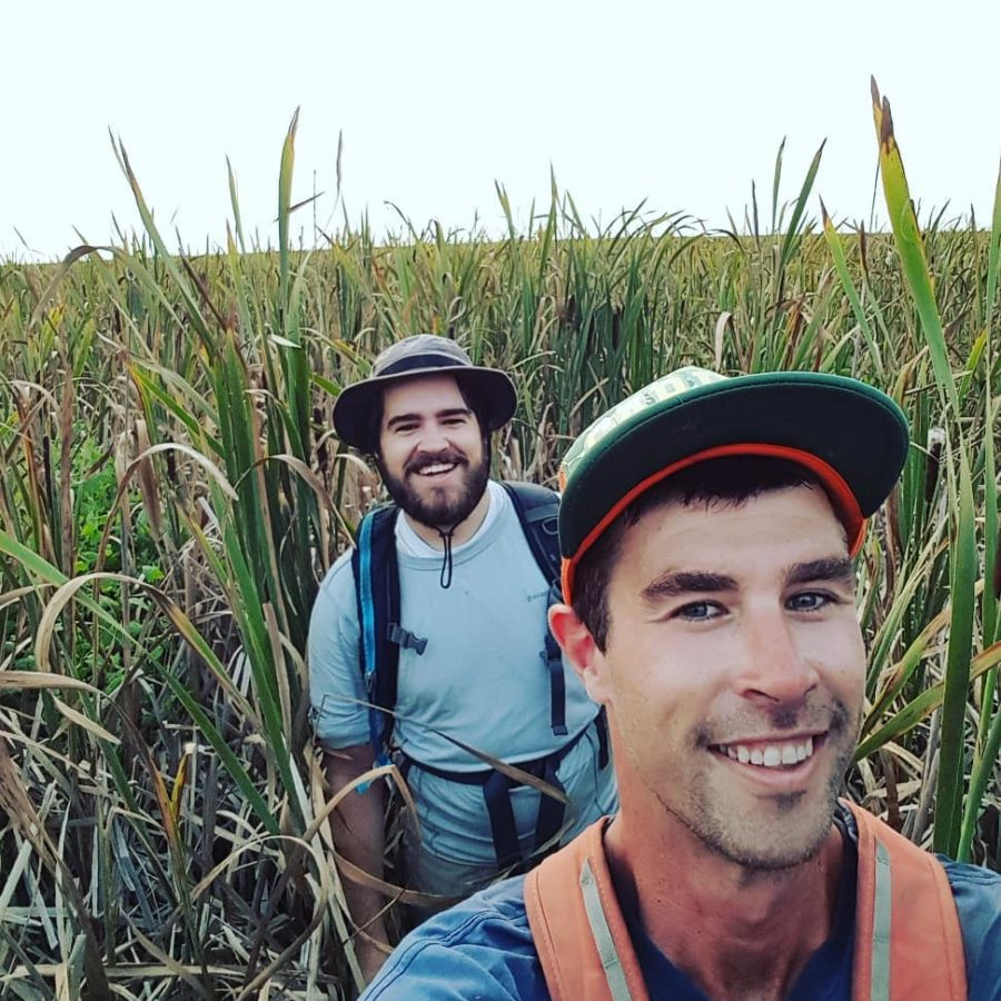 This is a selfie with two men standing in grass as tall as them. The one in front has a cap and orange vest, and the one slightly further behind has a beard and blue shirt. Both are smiling and it's a grey day.