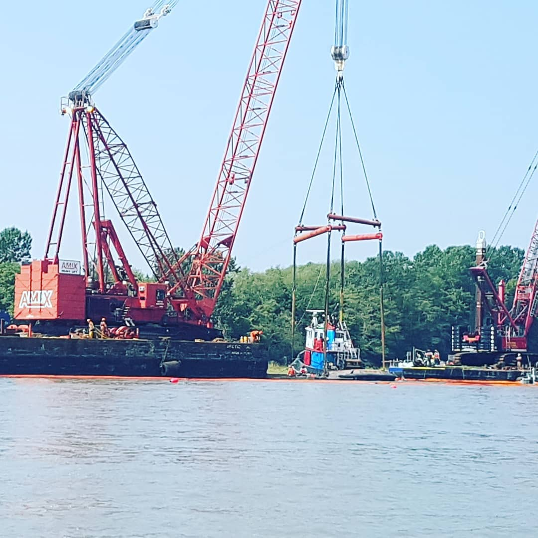 This is an image of a red crane lifting a tug boat from the water. It is a clear, blue day and behind this scene are low green trees.
