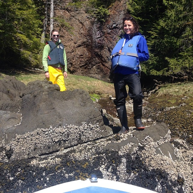 Two researchers Lia and Marlie are standing over a stream on rocks on Heiltsuk territory