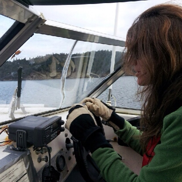 Raincoast staff Misty Macduffie pictured holding the steering wheel of a small boat, The Heron, as they leave Pender Island