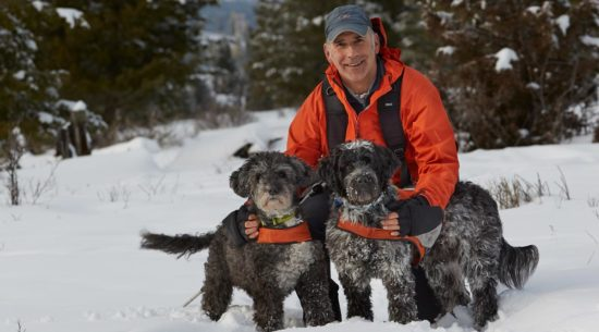 Brad Hill, photographer, with his dogs in the snow.