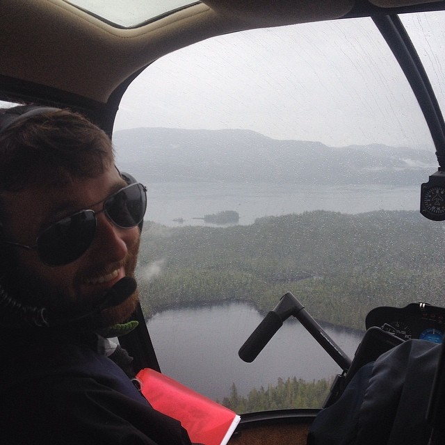 Profile of a scientist sitting in a helicopter and the view of a lake surrounded by mountains visible past him through the cockpit