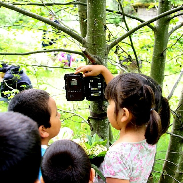 Elemtary school children from Wuikinuxv hold up a bear cam placed by Raincoast research to look for signs of grizzlies