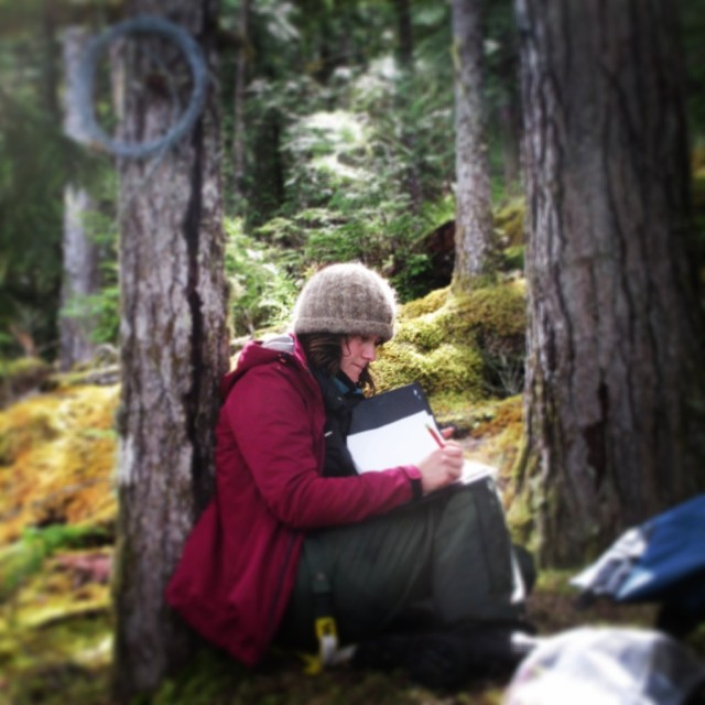 A woman sits leaning on a tree looking through her notes for Raincoast research