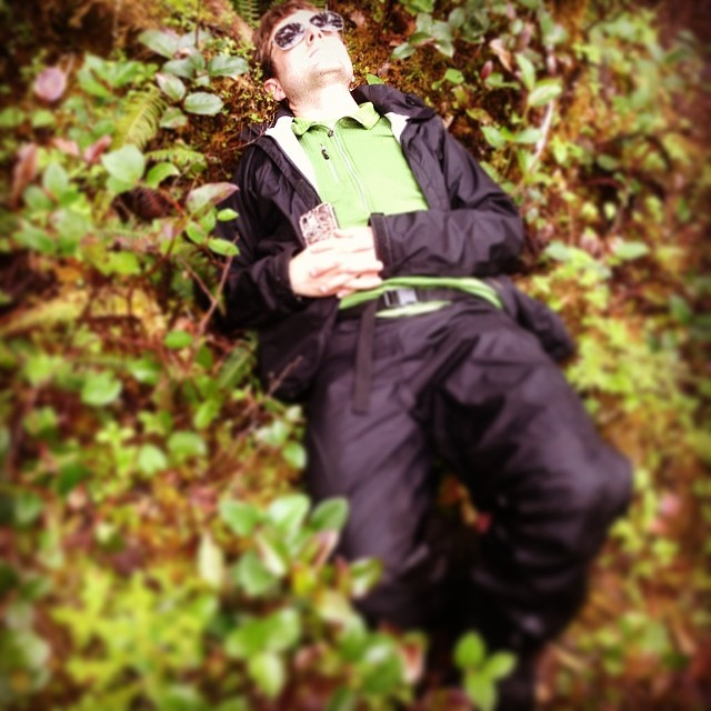 Man in sunglasses and black suit lies on the brown leaves and green shoots covered ground in the Great Bear rainforest, relaxing