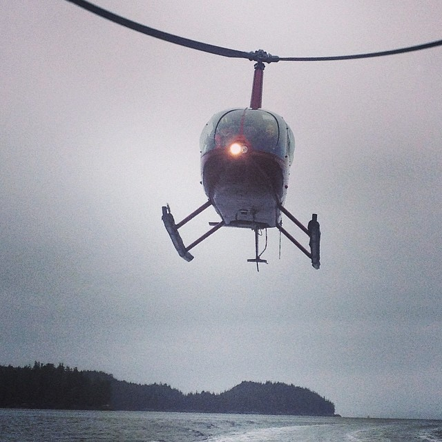 A helicopter hovers above water