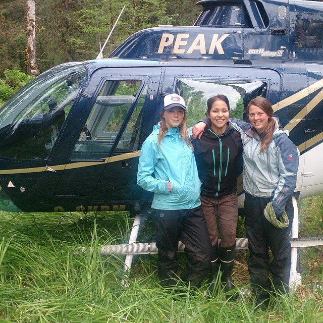 three women pose in front of a helicopter with the legend PEAK on it