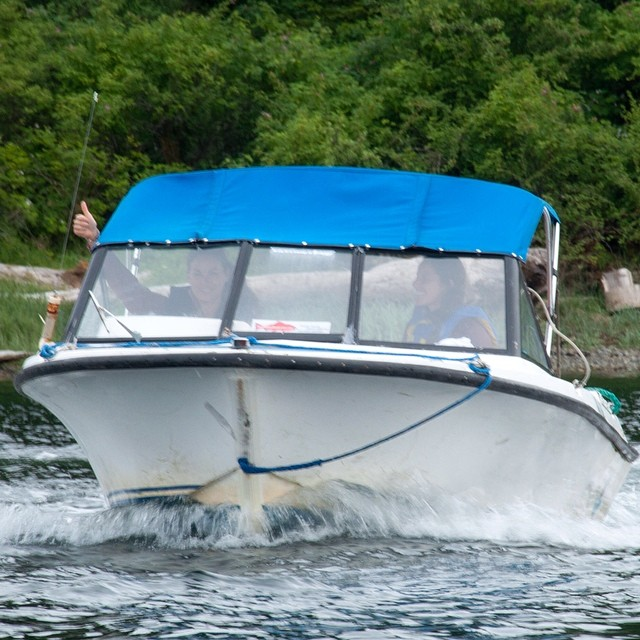 Two women driving a boat with blue trim show a thumbs-up sign as they speed away from an island
