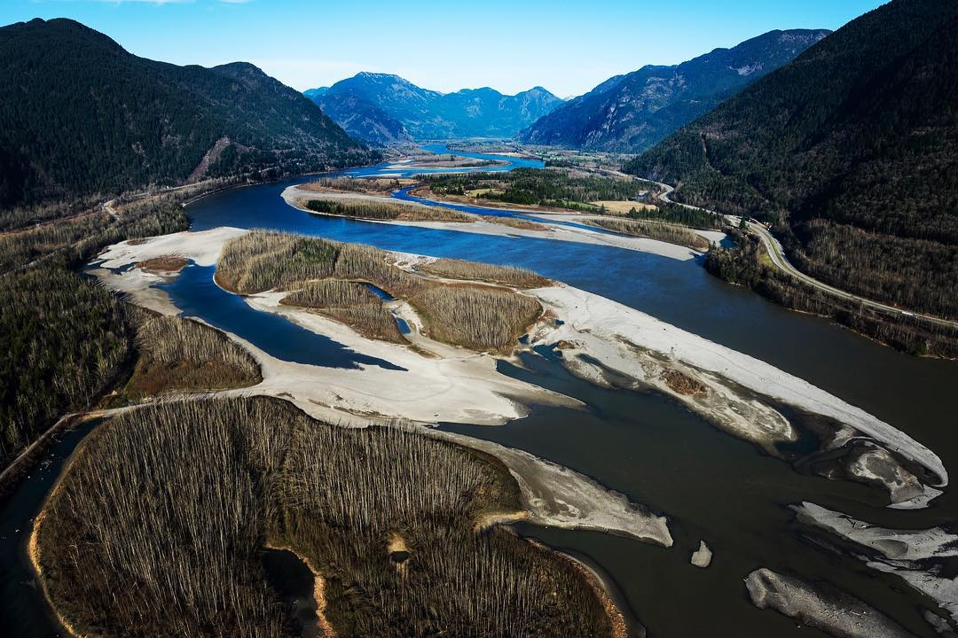 Aerial photogragh of a part or Fraser River, dark blue water meandering through brown and white lands and islands with mountain range in the background