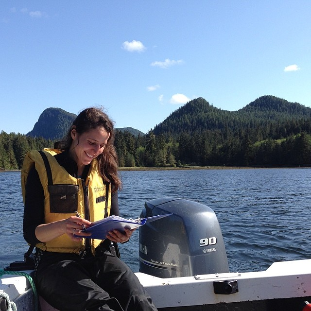Female person wearing yellow life jacket sitting on a boat with a notepad, doing science