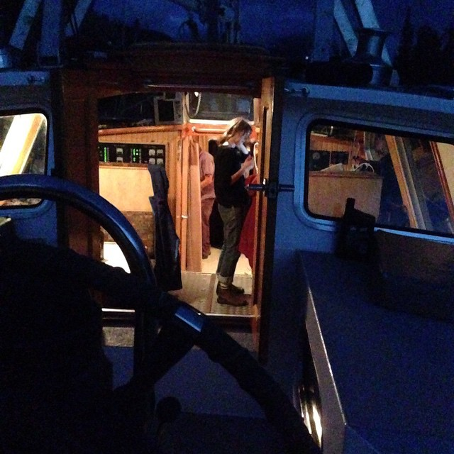 Nighttime darkness envelops the boat used by Raincoast staff the Achiever while a staff member stands inside