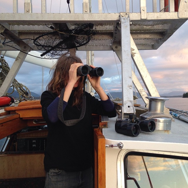 Staff biologist Misty Macduffee holds a binoculars to their face while on board the boat Achiever