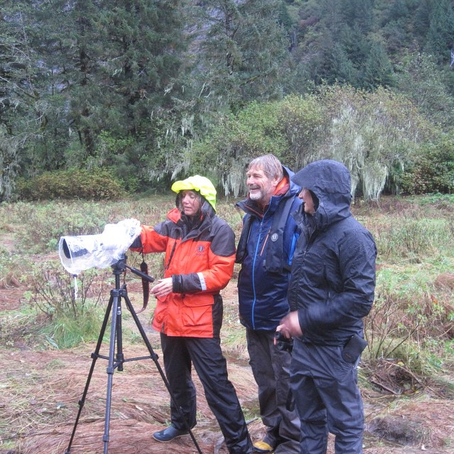 Three raincoast staff wearing rain jackets stand beside a video cmaera mounted on a tripod in the Great Bear rainforest
