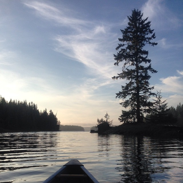Tip of the canoe visible in silhouette heading down the water