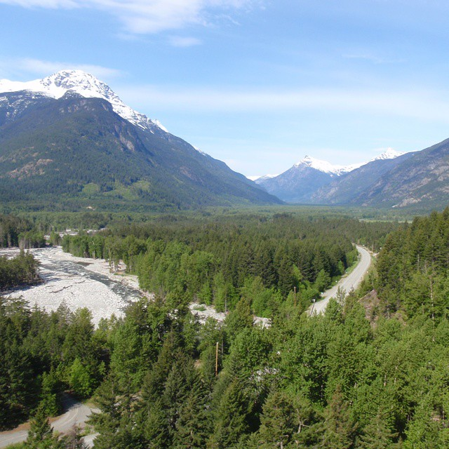 Forest, winding water and mountains against a blue sky in Nuxalk Territory