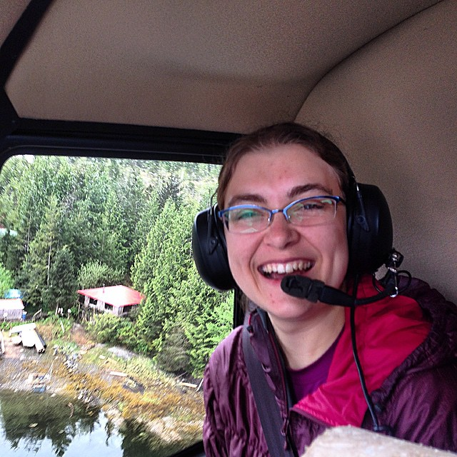 smiling face of staff member alena wearing headphones and gear aboard the helicopter, in the cockpit, with the forest visible outside the window