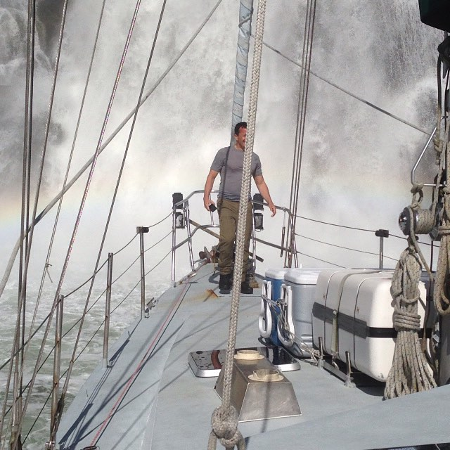 A man stands on the edge of a boat and gets sprayed on his back by a waterfall