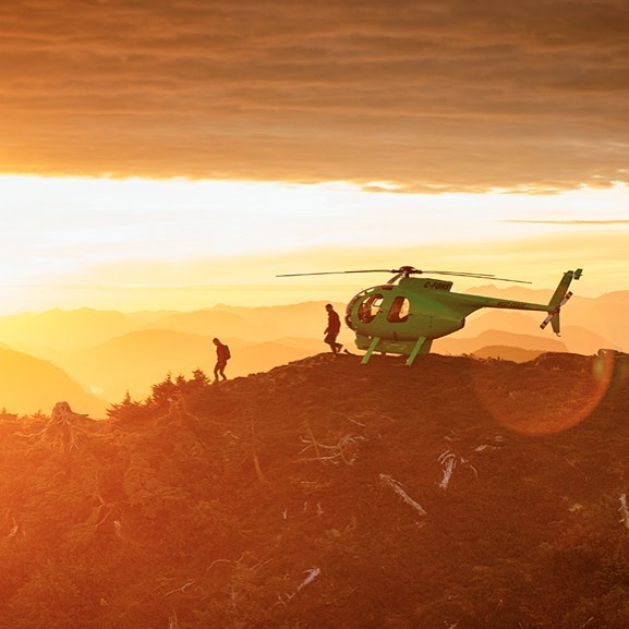 A helicopter landed on a hill and two people carrying backpacks leaving it, with sunset in the background and the image in sepia
