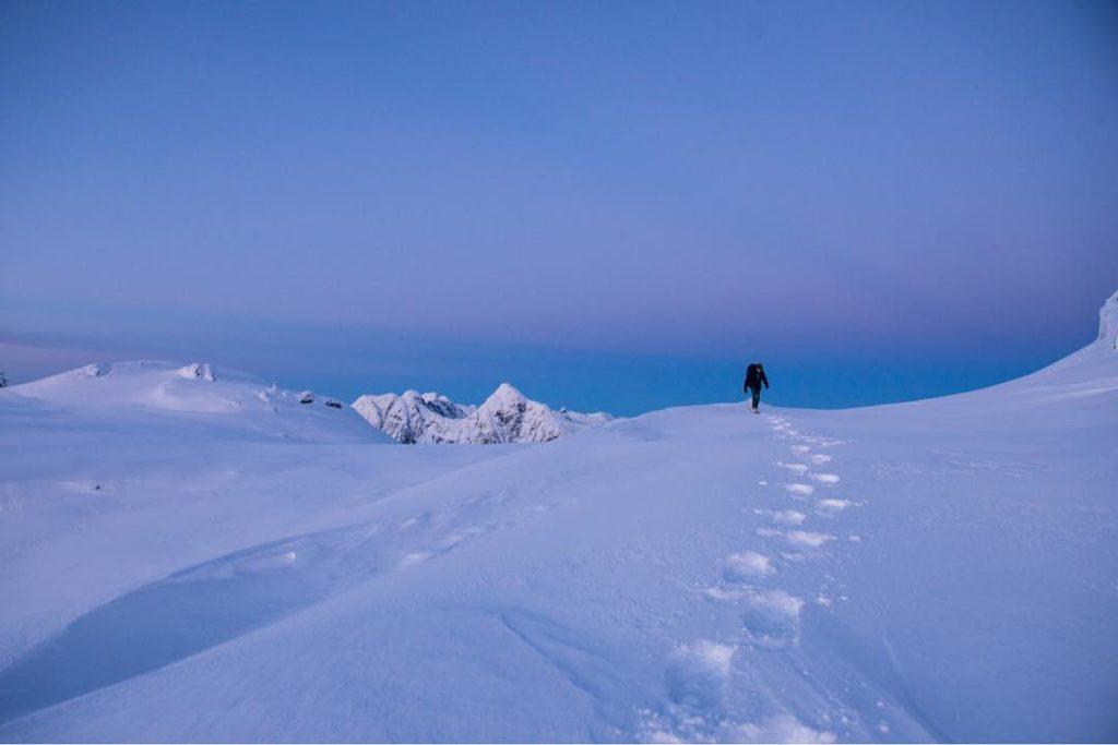 A person walks through the snow over a giant blue mountain near Whistler.