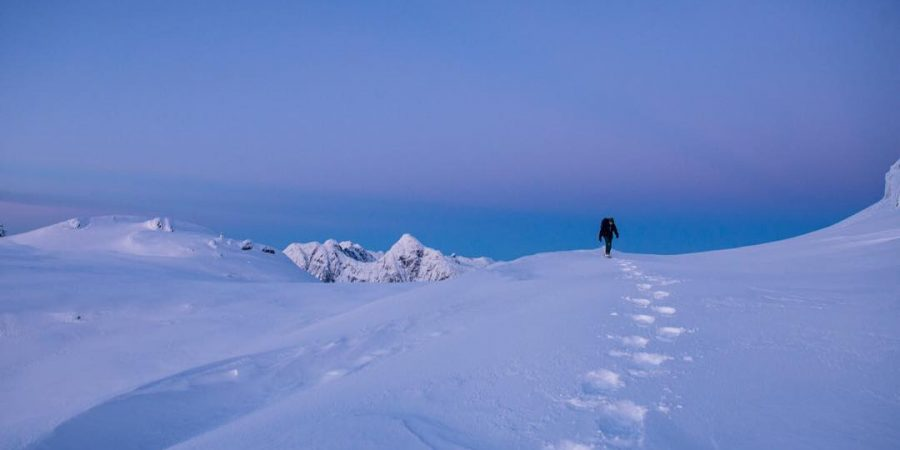 A person walks through the snow over a giant blue mountain near Whistler.