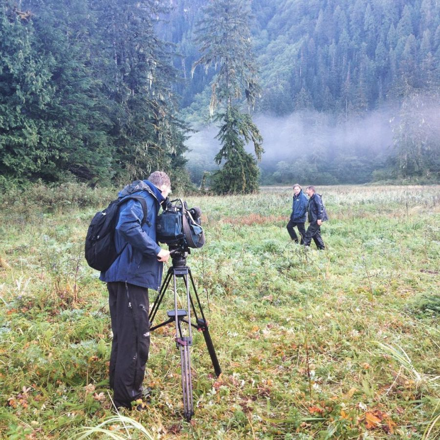 A camera person stands behind his camera on a tripod in a clearing in the forest while Raincoast staff Brian Falconer faces the camera