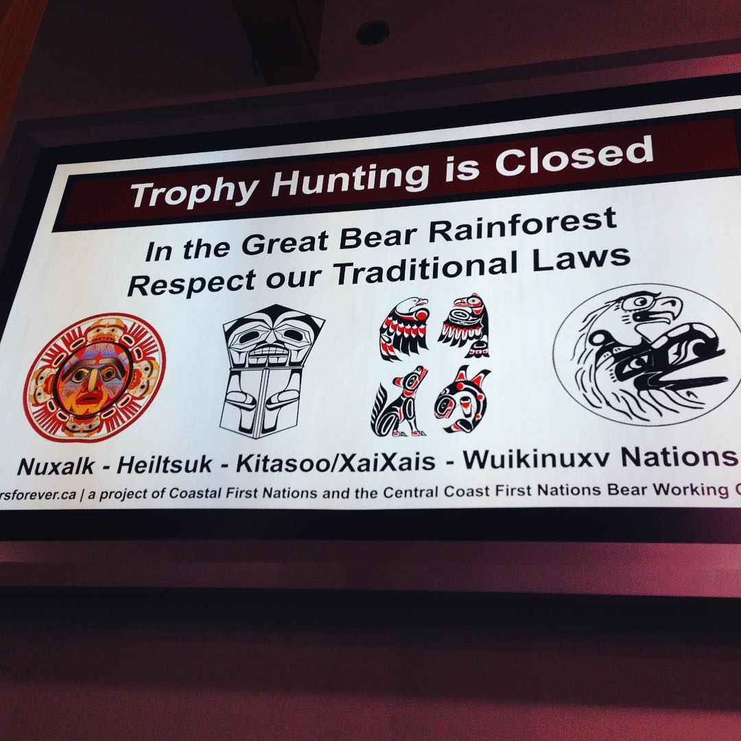 """A sign in the Vancouver terminal supplied by Coastal First Nations that reads """"Trophy Hunting is Closed in the Great Bear Rainforest. Respect our traditional laws. Nuxalk, Heiltsuk, Kitasoo/Xai'xai, Wuikinuxv,"""