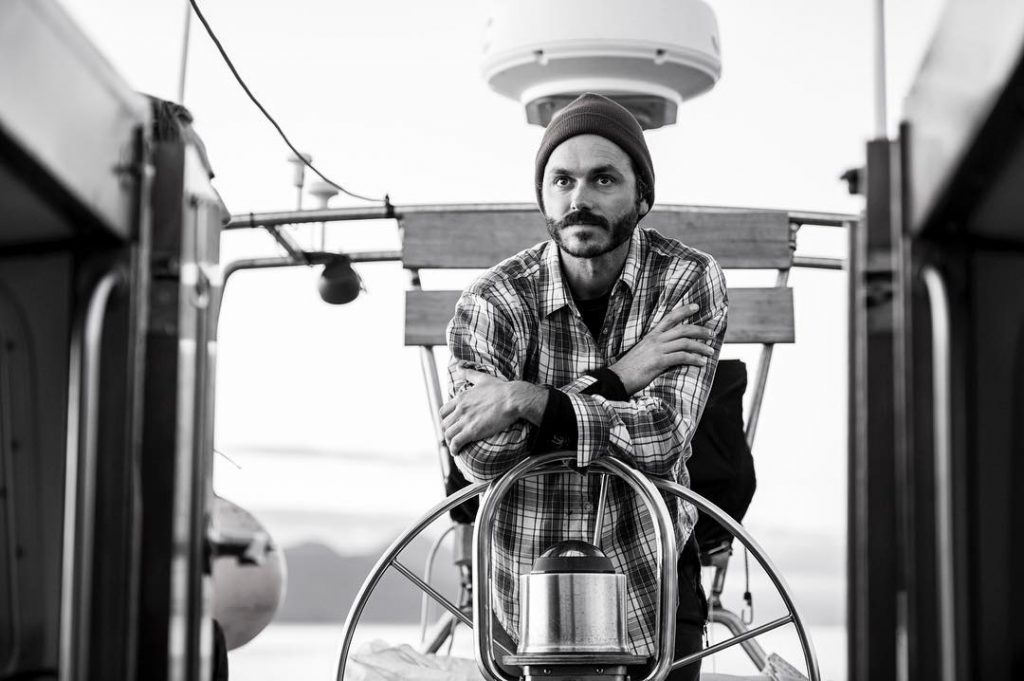Nicholas Sinclair, captain of Raincoast research boat Achiever pictured in black and white leaning on the wheel of the boat.
