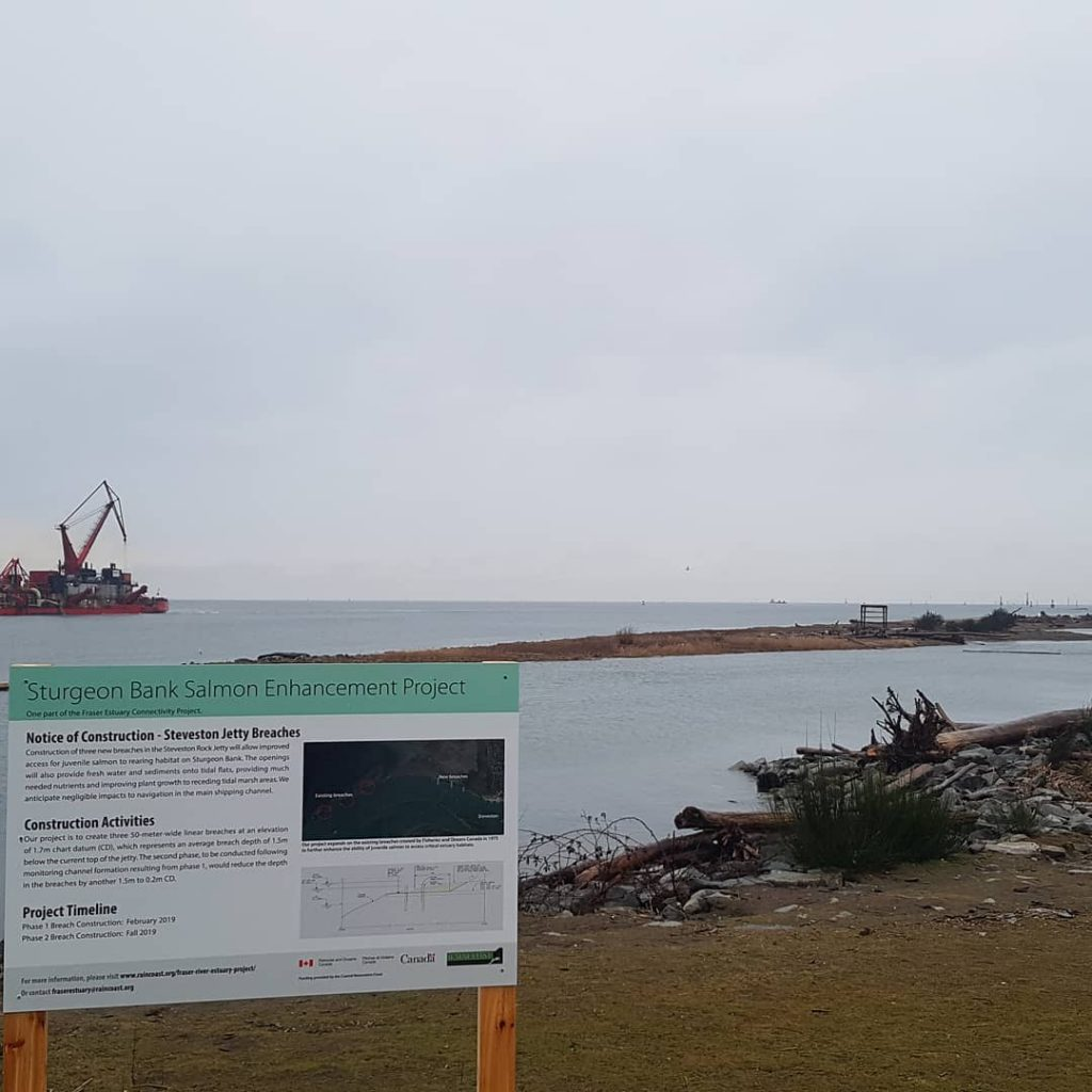 "A sign in the foreground says ""Sturgeon Bank Salmon Enhancement Project."" It is standing on a damp grassy stretch of land with driftwood and rocks further along. A body of water opens up to the right and there is a large red boat to the left behind the sign. It is a cloudy, grey day."
