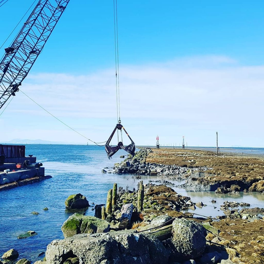 A metal crane hanging over down the center is coming from the left. It is hanging over a blue stretch of water that runs like a stream out to join a larger body of water in the distance. Moss and grass cover a stretch of rocky land to the right. The sky is blue with white clouds lower down.