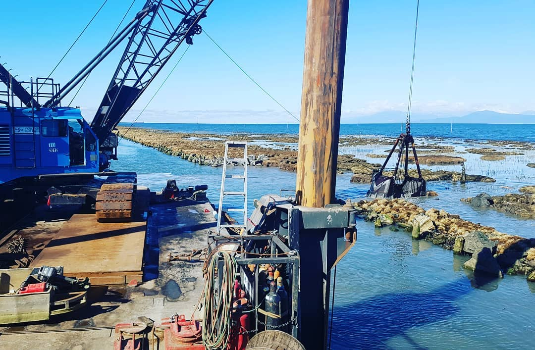 A wooden down with a crane on other machinery on it stands to the left in the foreground, the arm of the crane extends to the right over a body of water and there is rocky shore to the far right. The sky is clear and blue.