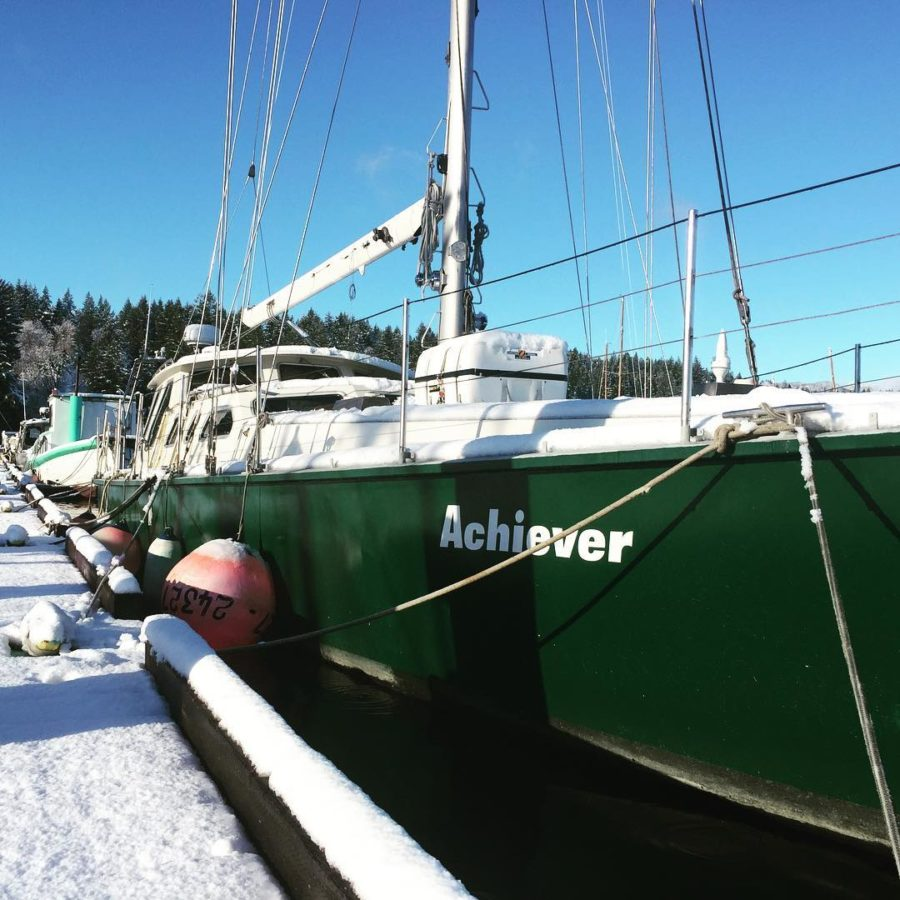 A green sail boat tied up at the harbour covered in snow. It says 'Achiever' in white letters on the haul.