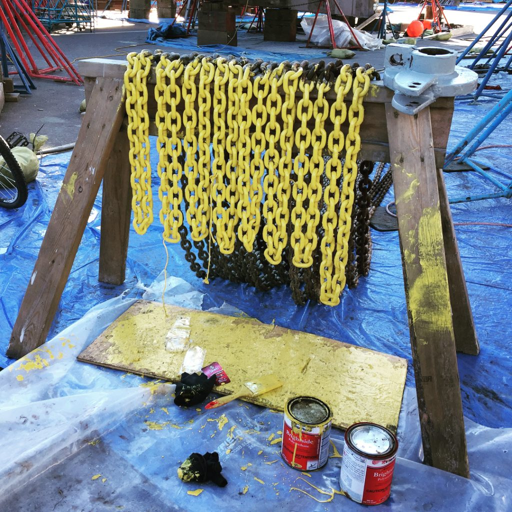 A row of painted yellow chains hang over wooden frame with blue tarp and paint cans underneath.