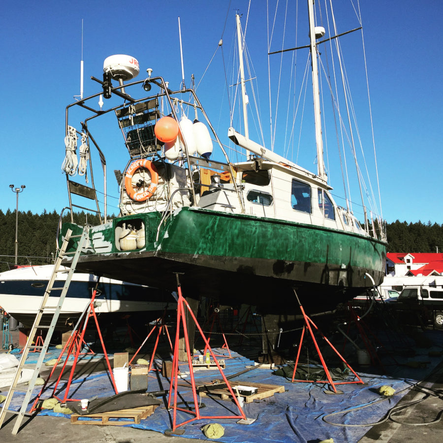 """A green boat lifted over a blue tarp with white writing on the side saying """"Achiever."""""""