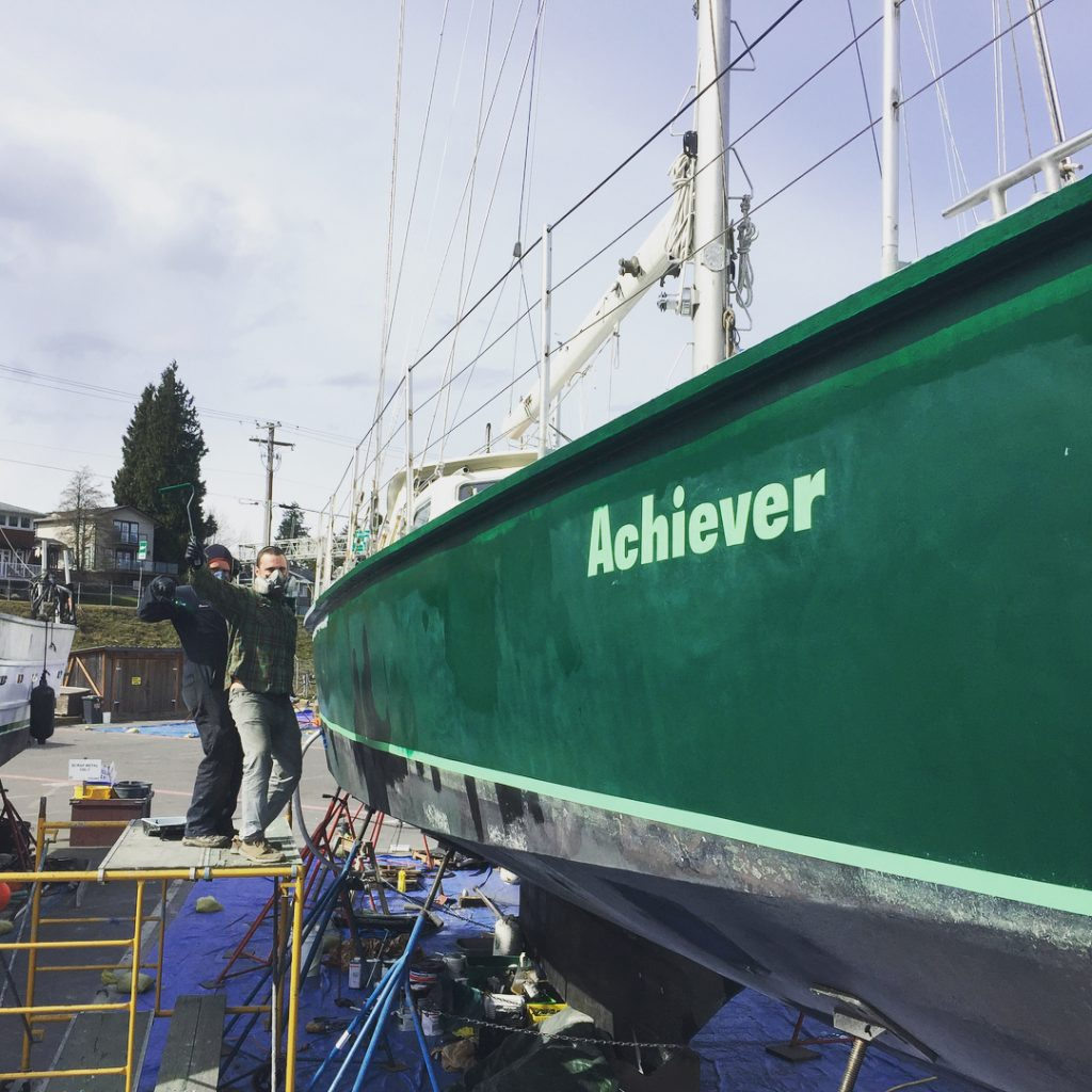 """A green boat lifted over a blue tarp with white writing on the side saying """"Achiever."""" Two masculine people stand on a ladder beside the boat making happy, funny faces."""