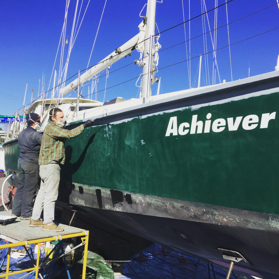 """A green boat lifted over a blue tarp with white writing on the side saying """"Achiever."""" A masculine person stands on a ladder beside the boat painting."""