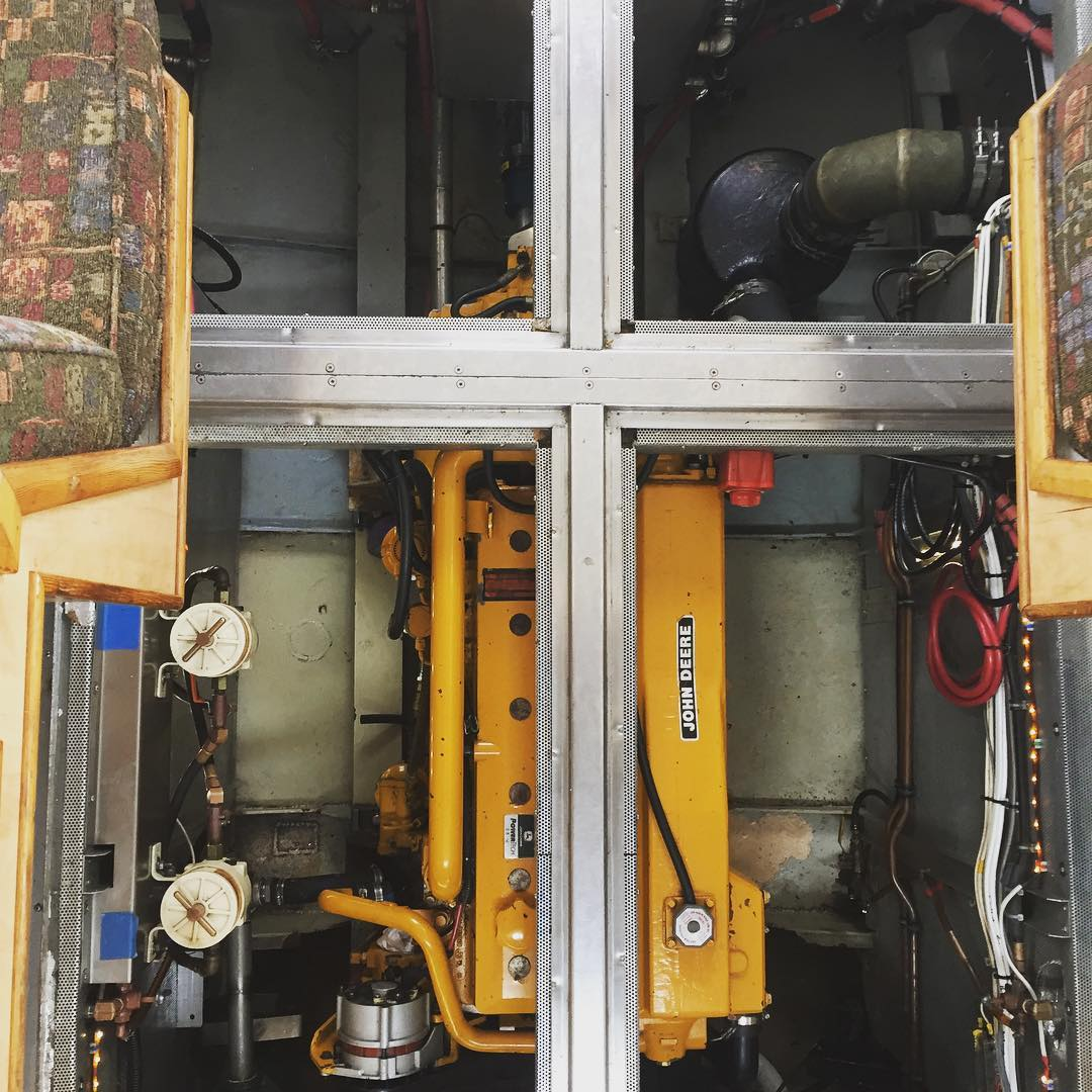The inside of an engine with silver bars in a cross shape in front of a yellow box.