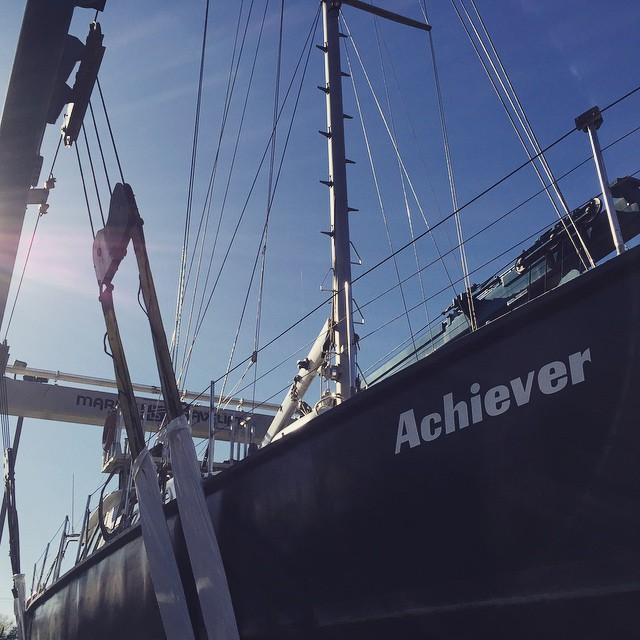 Looking up at a sail boat hull that says Achiever on the side.