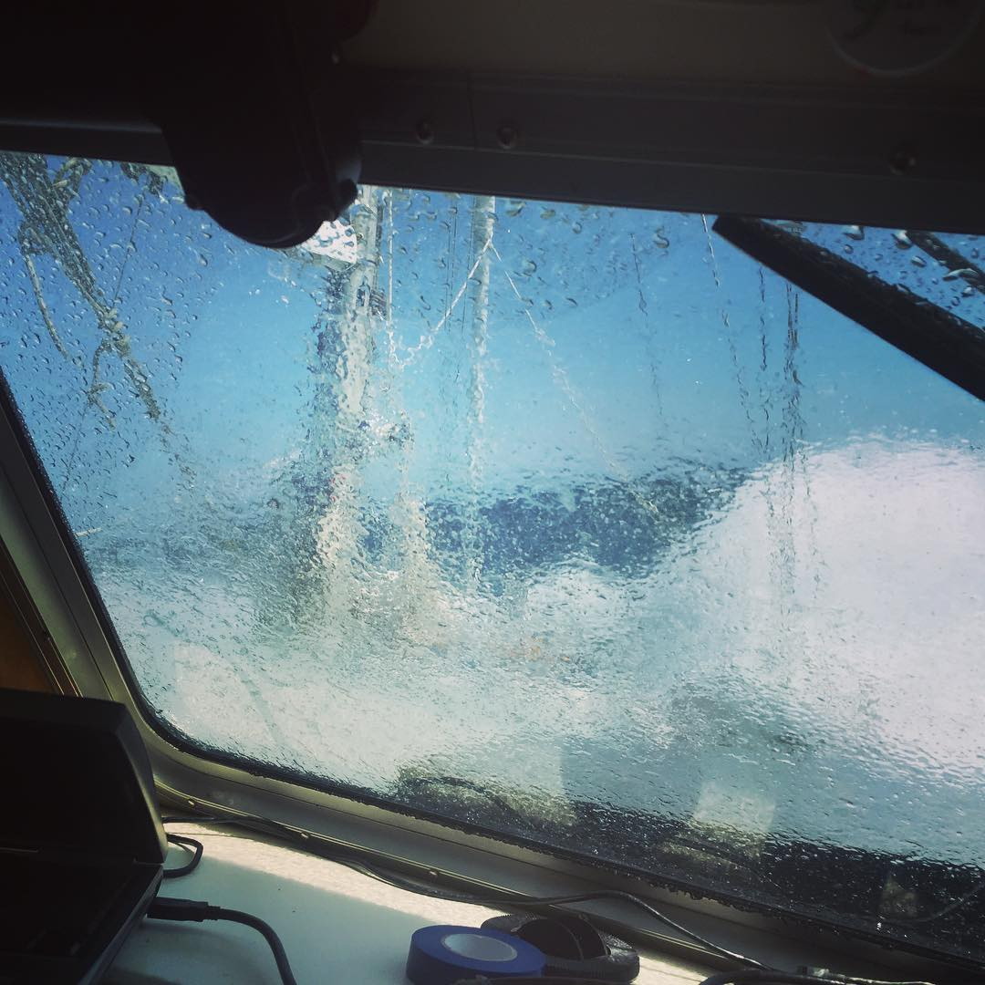 Looking out of the windshield of a sailboat splattered with ocean water.