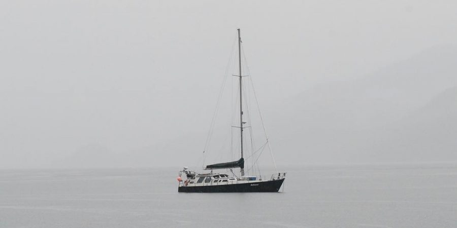 A white and green sailboat (the Achiever) on a grey ocean in torrential rail. The sky is grey and you can barely make out some land in the distance through the stormy weather.