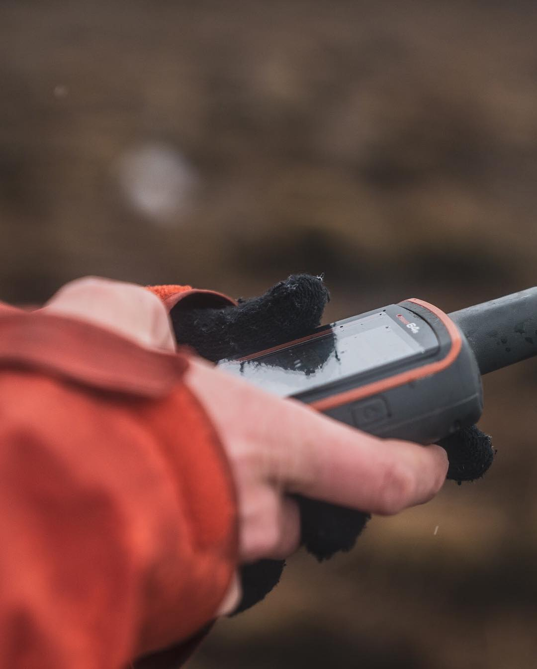 A hand with a bright orange coat sleeve holding a Walkie Talkie with dirt floor in the background.