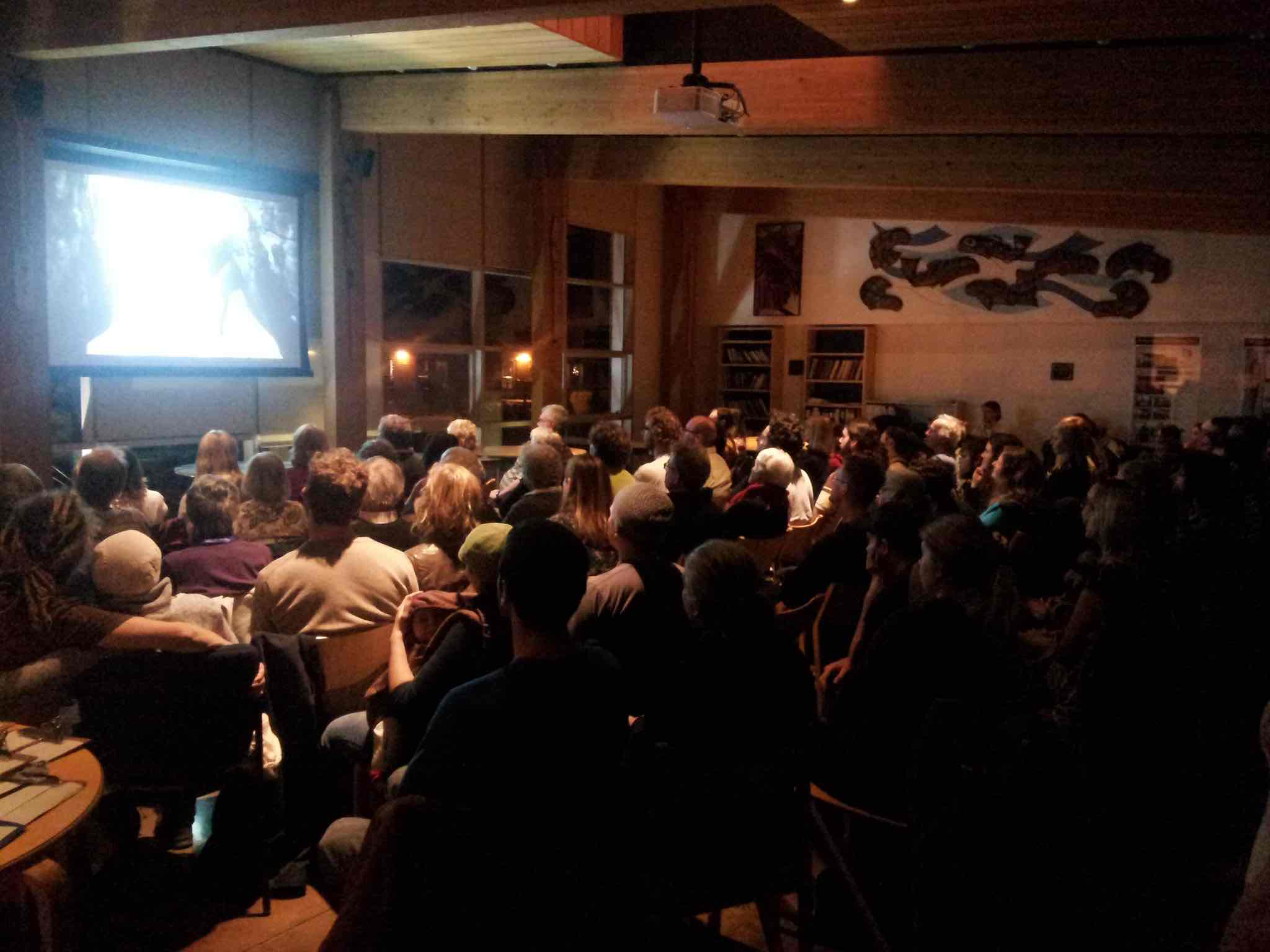 A wood panelled room full of people with a projector at the front.