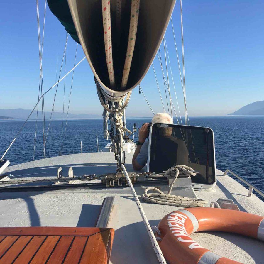 Looking out along the deck of a sail boat under a sail and out to sea.