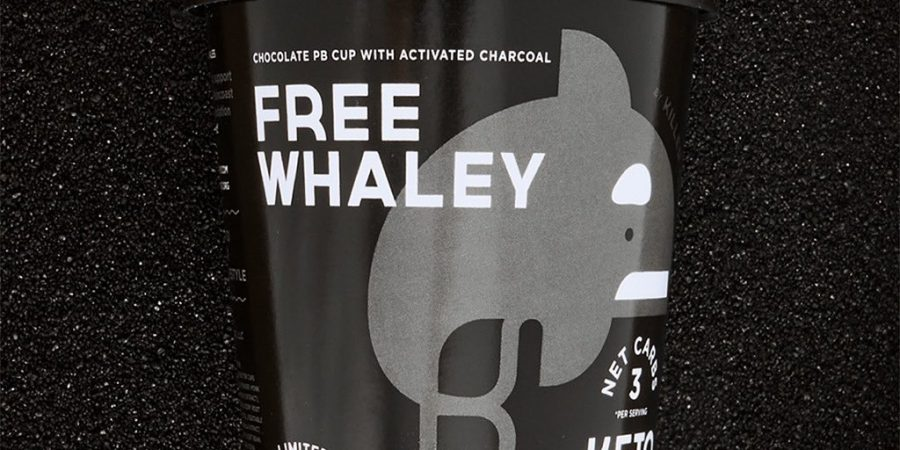 "A black icecream tub with an orca on it reads ""Free Whaley"" on a black backdrop."