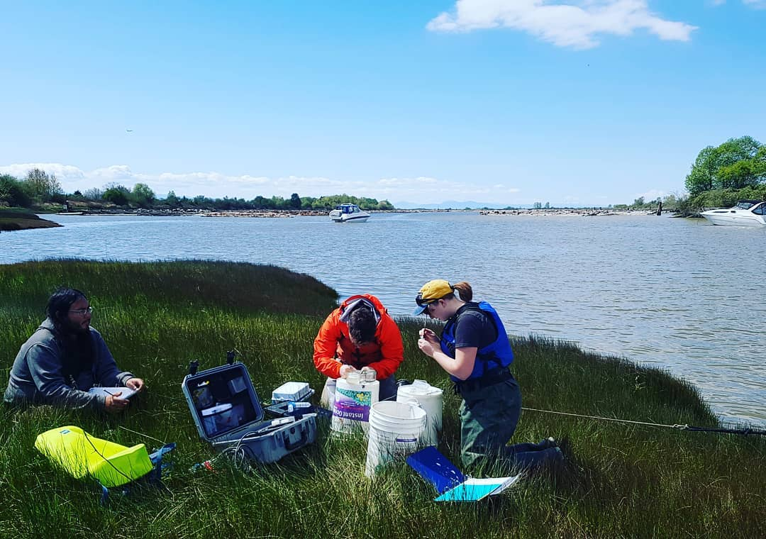 Two scientists sit on the grass of the banks of the Fraser River visible behind them with scientific equipment
